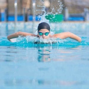Young girl in goggles and cap swimming butterfly stroke