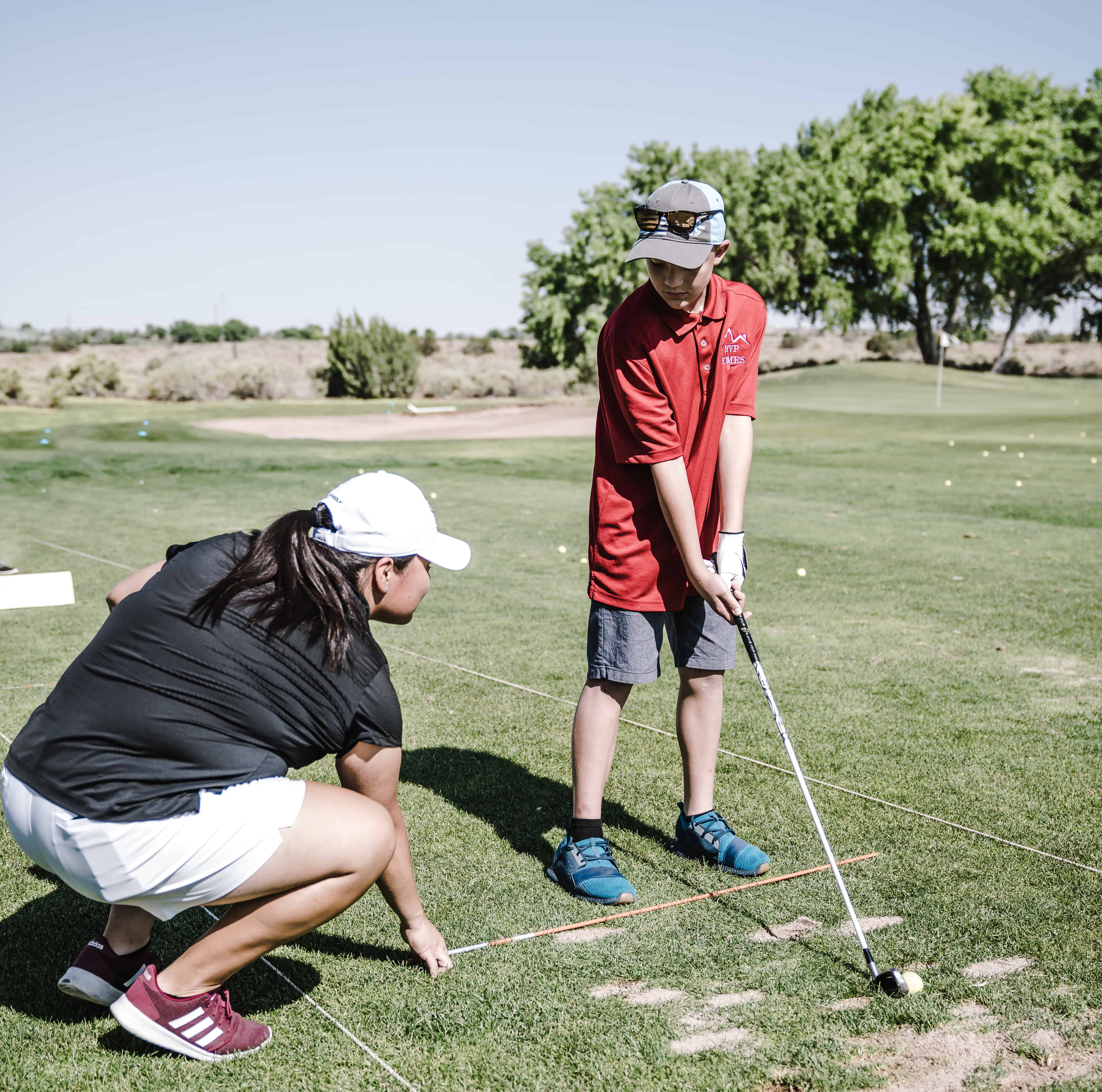 boy holding golf club in front of a crouchin woman to illustrate mind management