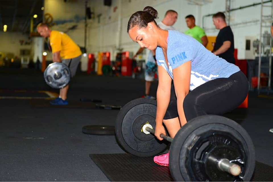 woman lifting weights, striving to increase focus