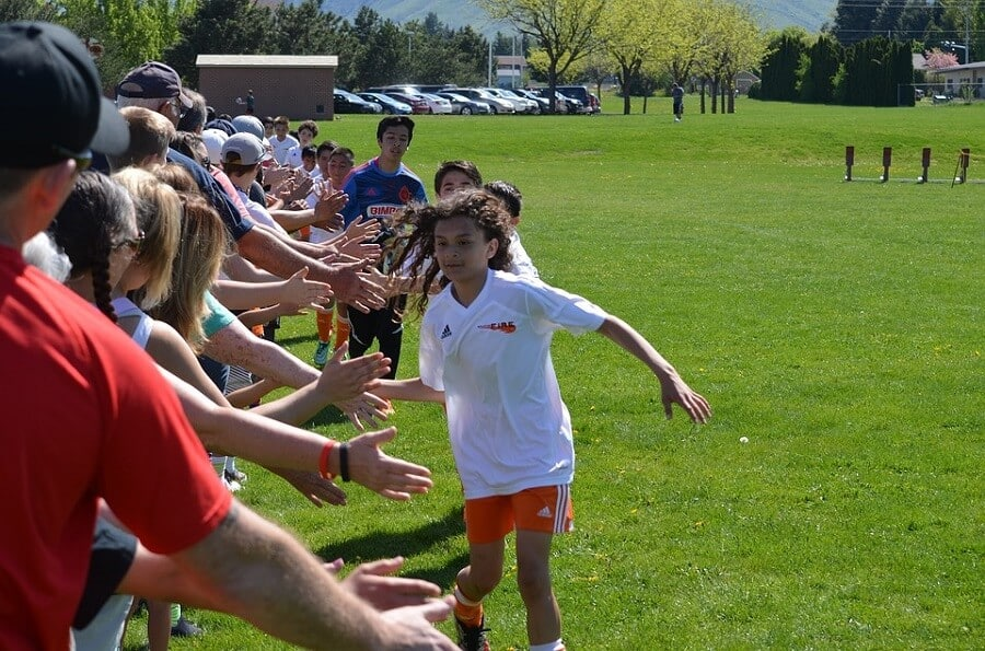 team of children showing good sportsmanship by high fiving the fans
