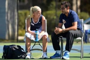 male tennis coach and female tennis player talking