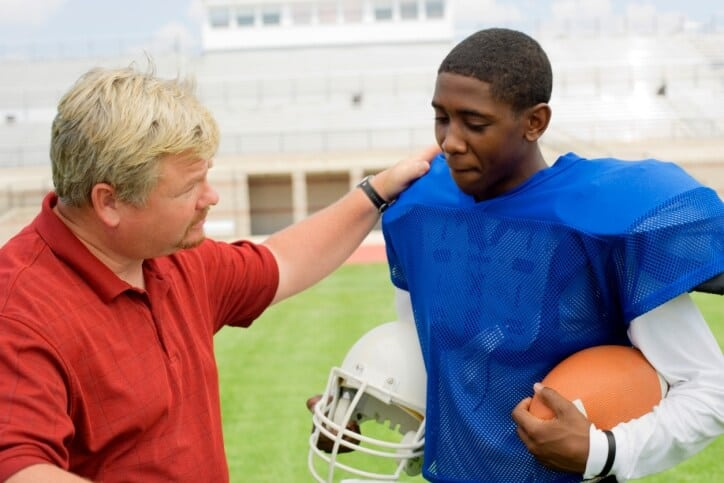 Coach comforting football player
